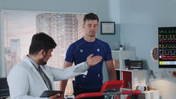 Stress testing in sports lab: doctor with tablet explaining athlete's EKG data Footage