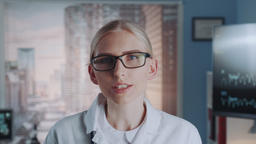 Profile view of smart female doctor in eyeglasses and lab coat telling something Footage