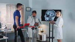 Multiracial doctors speaking about athlete's brain MRI on display Footage