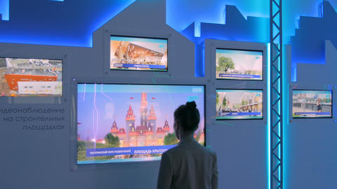 Woman using interactive touchscreen display at modern technology exhibition Footage