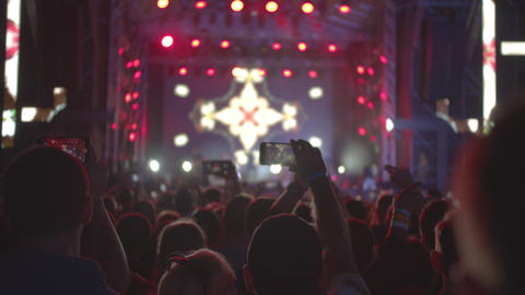 Night iconic concert. People cheer move and clap their hands in unison against Footage
