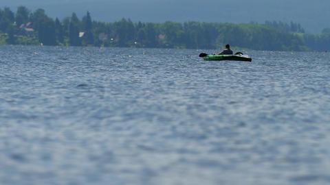 Boy in green kayak sail on pond. Sunny day on wonderful lake. 15th of July 2019, Lipno lake, Czech Live Action