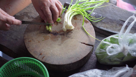 Scallion and coriander get chopped by old lady with cooking knife Live Action