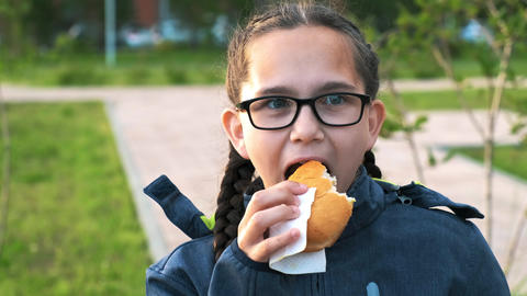 Portrait of a schoolgirl with glasses eating a hamburger Footage