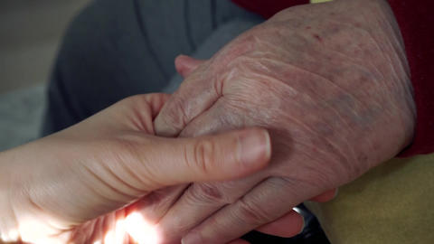 The hand of a young girl holding the hand of an elderly person (her grandmother). Sign of love, Footage