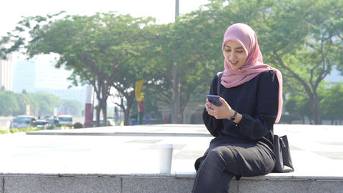 Muslim woman using smartphone and laughing alone Live Action