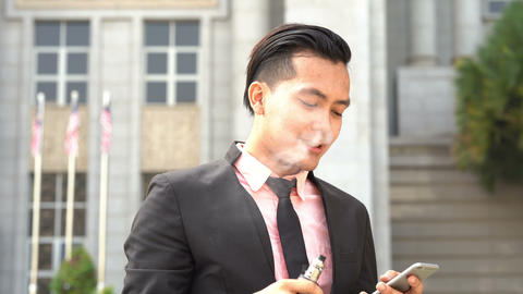 Asian business man vaping outside office Live Action