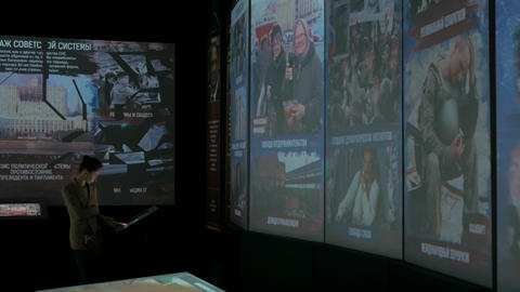 Woman using interactive touchscreen display at modern history museum Live Action
