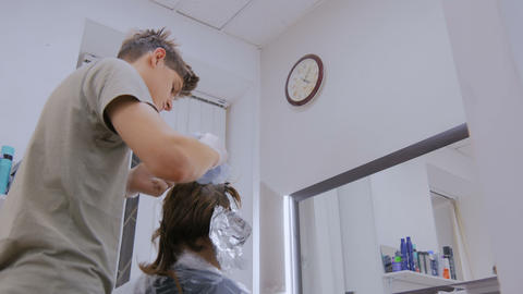 Professional male hairdresser coloring hair of woman client at studio Footage