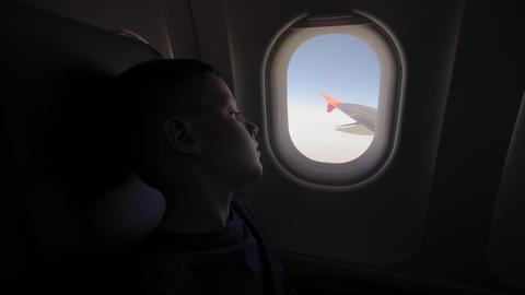 The small boy looks to the plane window to the wing plane Live Action