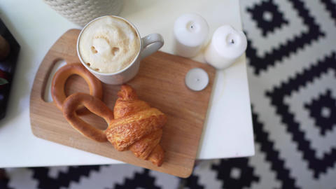 Coffee and fresh pastries on a table with candles. Morning Autumn or Winter Day Footage