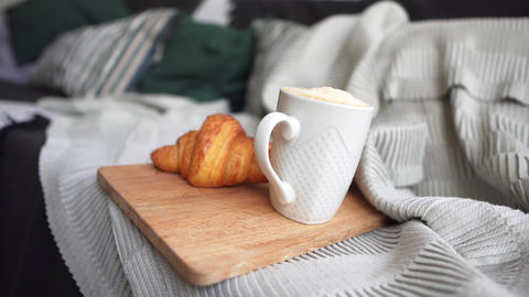 Coffee in a white cup and a fresh croissant on a cozy sofa. Breakfast on a cold Live Action