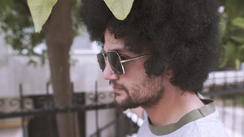 Curly man in street, summer times Footage