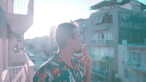 Handsome young man takes a cigarette and light it up. Cool man smokes and wearing floral shirt Footage
