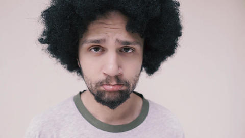 Portrait of sad african american curly man looking at camera. Close-up young afro man portrait Live Action