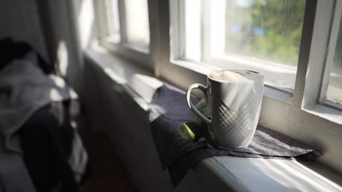 Lagom or Hygge concept - white cup of hot coffee on a windowsill in the sun Footage