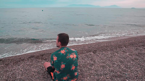 Young man sitting on the beach and looking at the sea at sunset. Handsome man enjoys the nature and Footage