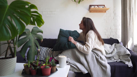 Hygge or Lagom concept - beautiful woman resting on the couch. Comfort and Footage