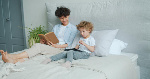 Young woman and small boy using tablet in bed smiling enjoying gadget together Live Action
