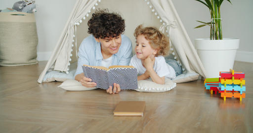 Loving mother reading book to cute child lying on floor in cosy tent indoors Footage