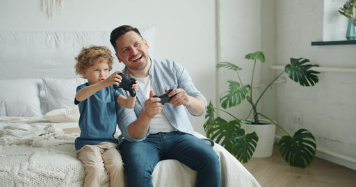 Slow motion of man and boy playing video game having fun sitting in bed at home Footage