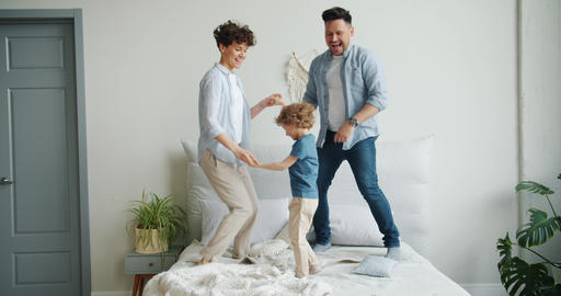 Man and woman jumping dancing on bed with happy child having fun at home Footage