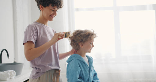 Caring parent brushing small boy's hair with hairbrush in bathroom at home Footage
