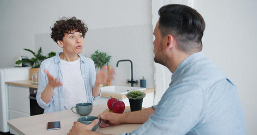 Slow motion of angry woman arguing with husband at home at kitchen table Footage