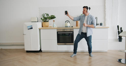 Guy in headphones listening to music dancing in kitchen at home with smartphone Footage