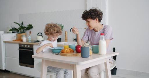 Slow motion of happy mother and son eating cereal with milk at home talking Footage