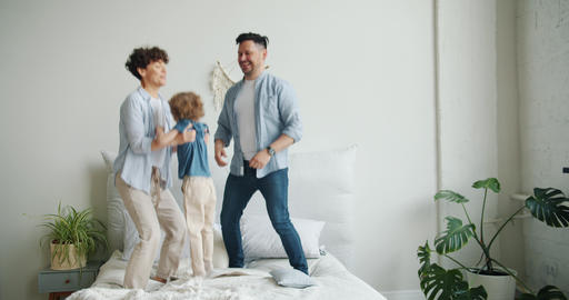 Mother father and son jumping dancing on bed in bedroom at home together Footage