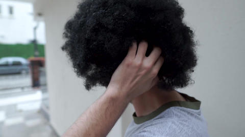 Young man scratching his head and fluffy curly black hair Live Action