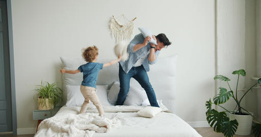 Father and son playing on bed fighting pillows falling then mother coming home Footage