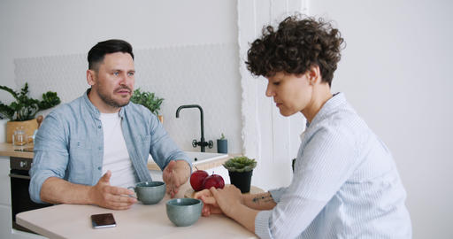 Slow motion of angry man yelling at unhappy wife sitting in kitchen at table Footage