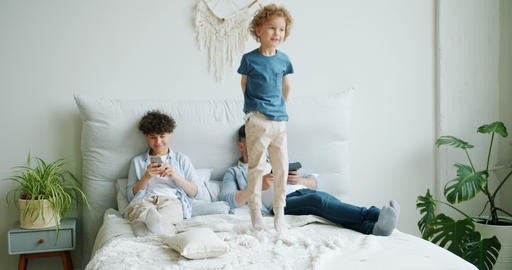 Naughty child jumping on bed while parents using gadgets relaxing in bedroom Live Action