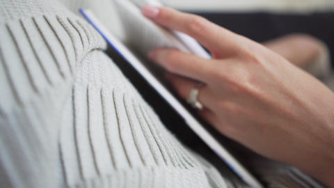 Close-up - woman leafing through pages of a book, holding it on a cozy plaid Live Action