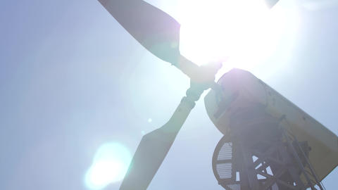Flickering bright sunlight through the blades of a wind turbine against a blue Footage