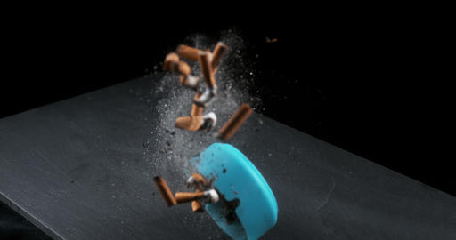 Ashtray filled with Megots falling on Black Background, Slow Motion 4K Live Action