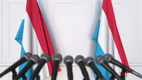 Luxembourgian official press conference. Flags of Luxembourg and microphones Live Action