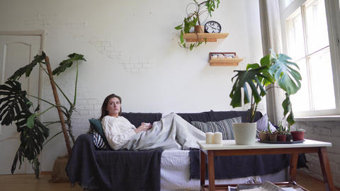 A young woman on the couch enjoys relaxing - drinks a hot drink, wraps herself Live Action