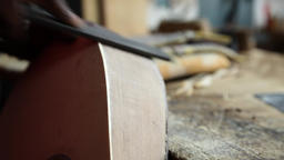 worker sanding wood with wood file from a construction guitar, slider shot Footage
