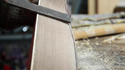 Craftsman sanding wood with wood file from a construction guitar Footage