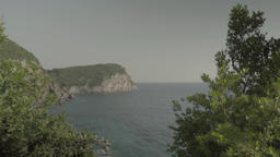 The sea near the shore with rocks and trees. Marine and coastal landscape Footage