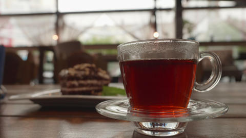 Cup of hot tea with smoke in transparent cup on saucer in cold room with cake Live Action