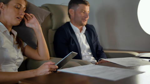 Confident rich colleagues discussing about business during first class flight Live Action