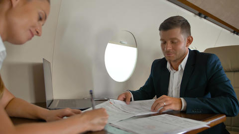 Businessman and businesswoman inside of modern luxury private jet signing big Footage