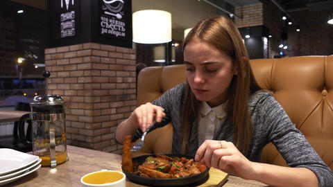 Portrait of young girl eats tasty fried potato served on a pan in city cafe Footage