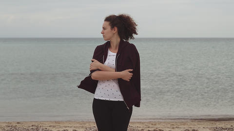 Young woman standing in cold weather by the sea and dress herself with sweatshirt Live Action