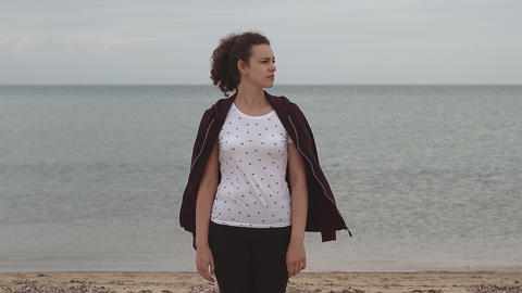 Young woman standing in cold weather by the sea and dress... Stock Video Footage