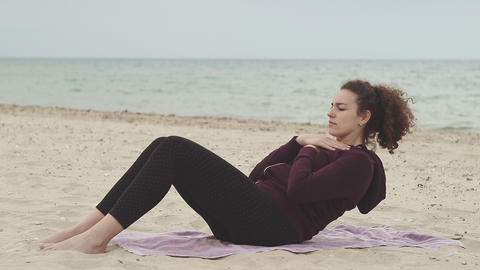 Fitness, sport and healthy lifestyle concept. Young woman doing Sit-up exercise on the beach. Young Live Action